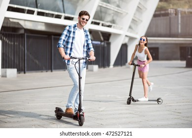 Joyful friends riding kick scooters