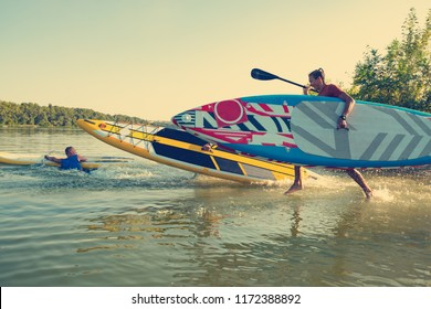 Joyful friends with SUP boards in their hands are running to the water in the summer evening and having fun. Stand up paddle boarding - awesome active outdoor recreation.