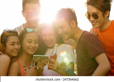 Joyful friends using application on the smartphone