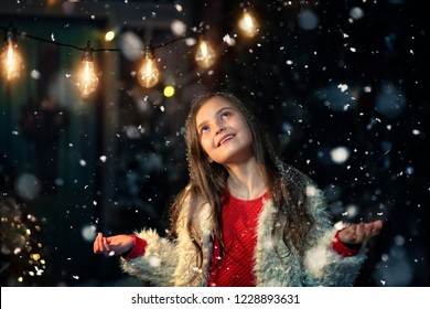 joyful fun of a young girl in a winter and snowy evening