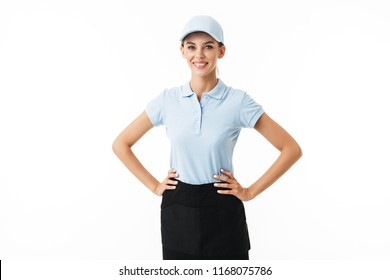 Joyful girl in blue polo T-shirt and cap happily looking in camera over white background