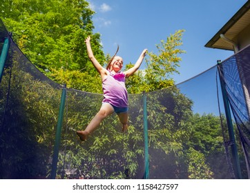 Joyful girl bouncing around a trampoline outdoors