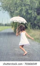 Joyful girl dance with umbrella in rain