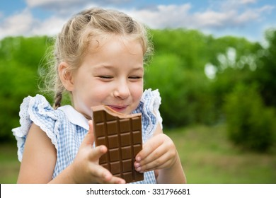 Joyful girl eating chocolate in the park.