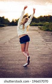 Joyful girl goes into the sky with raised hands