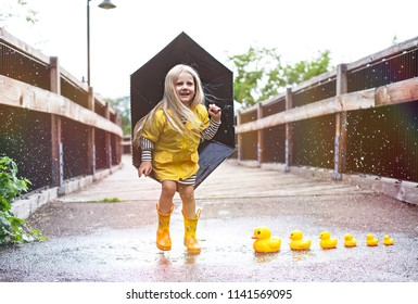 Joyful girl jumping on puddle with ducks next to it
