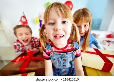 Joyful girl looking at camera with her happy friends on background