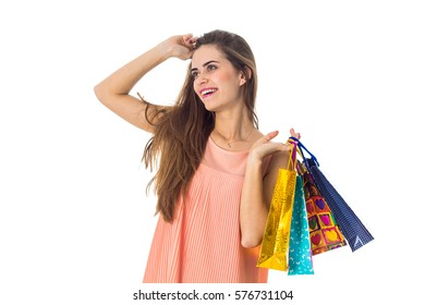 joyful girl looks away and keeps the color packages from stores isolated on white background