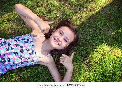 joyful girl is lying on the grass with a thumb up