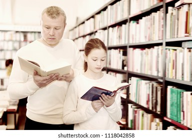 Joyful girl with man choosing and discussing books in bookshop