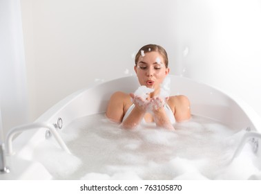 Joyful girl is playing with foam while taking a bath at spa