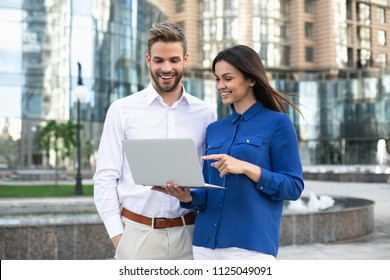 Joyful girl is pointing finger at computer screen while standing on street with her colleague. They are discussing project together with aspiration