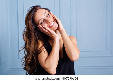 Joyful  girl posing on blue background, touching her face, enjoying life with closed eyes. Entertainment and leisure time.