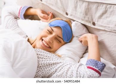 Joyful girl relaxing in bedroom