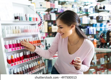 Joyful girl selecting nail polish from multicolored palette in drugstore