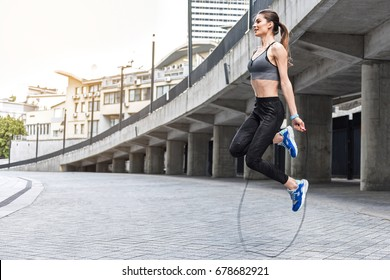 Joyful girl skipping on rope near stadium