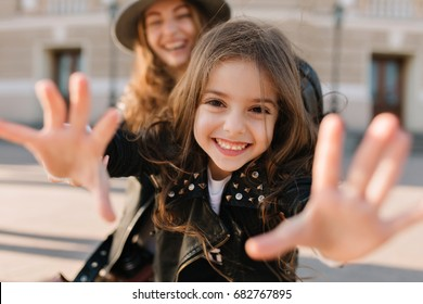 Joyful girl smiles charmingly and extends her hands to the camera, while her mother standing behind. Happy beautiful woman in hat spending time with excited daughter and having fun outside on weekend.