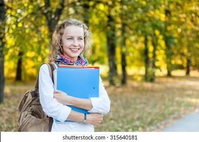 Joyful girl student with folders in the autumn park