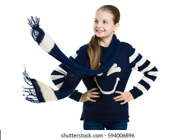 Joyful girl in sweater and scarf posing in the studio. Scarf flying in the wind. Girl looking away. Isolation on a white background