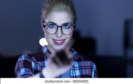 Joyful IT girl testing artificial intelligence in the dark lighted room