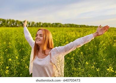 Joyful girl at yellow rape seed meadow