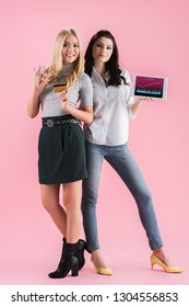 Joyful girls holding digital tablet with traiding app on screen and credit card on pink background
