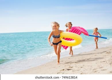 Joyful girls in swimwear running at tropical beach