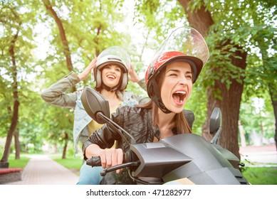 Joyful girls traveling by scooter