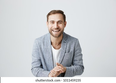 Joyful glad european bearded cheerful man being satisfied with results of work, smiles broadly at camera, keeps hands together, isolated against gray background. Caucasian male has good mood.