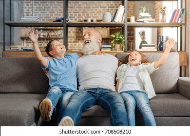 Joyful grandfather and his grandchildren laughing on sofa