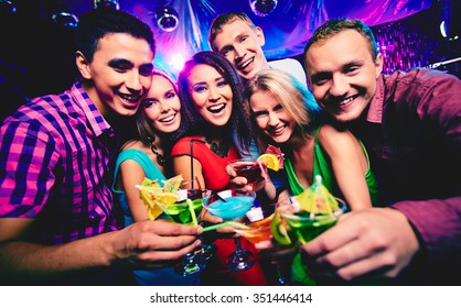 Joyful group of friends toasting with cocktails at party