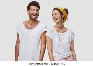 Joyful groupmates rejoice successfully passed exam, look happily at each other, laugh at good joke, express positive emotions, isolated over white studio wall. Husband and wife glad to have day off