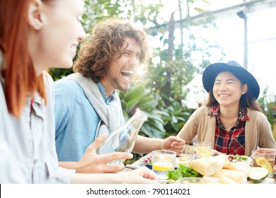 Joyful guy with bottle of lemonade laughing during talk to his friends by festive table