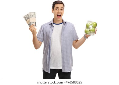 Joyful guy holding bundles of money and a pack of apples isolated on white background
