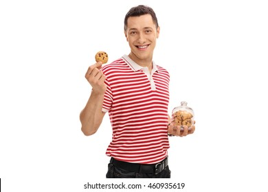 Joyful guy holding a jar with chocolate chip cookies in one hand and a single cookie in the other