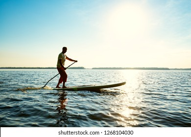 Joyful  guy paddling on a SUP board on a big river. Stand up paddle boarding - awesome active outdoor recreation and training.