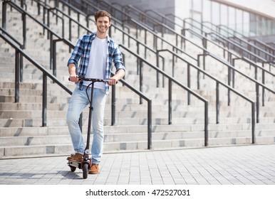 Joyful handsome man riding a scooter