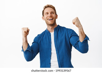Joyful handsome man watching sports game and rooting for team, raising hands up as winning, looking up at tv screen and smiling pleased, standing against white background