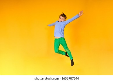Joyful and happy boy expresses his emotions in a jump, a child is jumping on a yellow background.