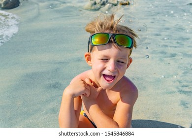 A joyful and happy boy in sunglasses on his head sits on the sea sand on the beach, smiles and looks around.