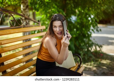 Joyful and happy business woman sitting on a bench with a bag hiding behind a tablet