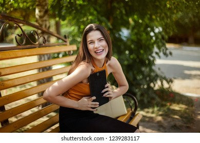 Joyful and happy business woman with a tablet sits on a bench with a bag. gadget in hand