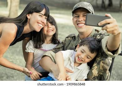 Freuen Sie sich auf einen glücklichen, behinderten Militärangehörigen, der sich mit seiner Frau und zwei Kindern im Park selbst abspielt. Konzept der Familienzusammenführung und Unterstützung