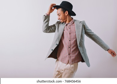 Joyful happy man wears black hat and grey suit dancing with excited emotions on the background of white wall, isolated background, place for text