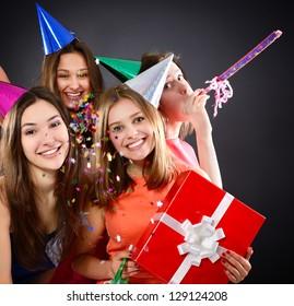 Joyful happy smiling teen girls have fun on birthday party, over black