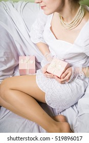 Joyful happy woman holding gift box over light chair bed background. Closeup image