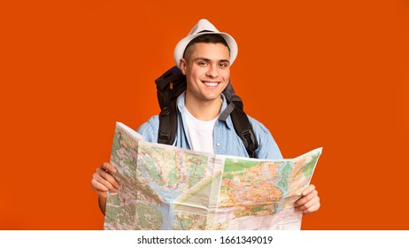 Joyful hiker with big backpack holding map over orange studio background