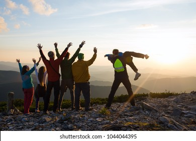 Joyful hikers, friends with open arms are standing on a top, admiring the panorama of mountains in the rays of setting sun and having fun. Epic adventure in a wilderness. Back light, back view.