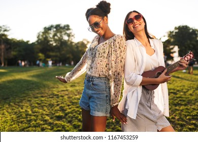 Joyful international girls in sunglasses happily playing on little guitar and dancing spending time together in city park on sunset