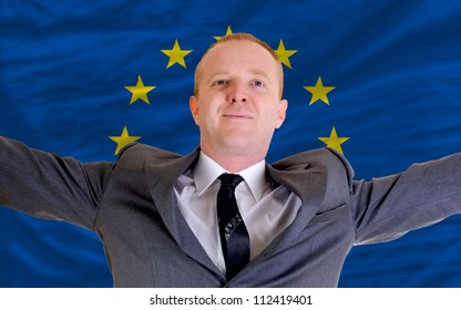 joyful investor spreading arms after good business investment in europe, in front of flag